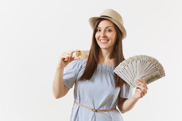 파란 드레스를 입은 젊은 여성, 긴 머리에 달러 묶음, 현금 돈, 비트코인, 흰색 배경에 격리된 황금색 동전을 들고 있는 모자. 금융, 비즈니스, 가상 통화 개념입니다. 복사 공간