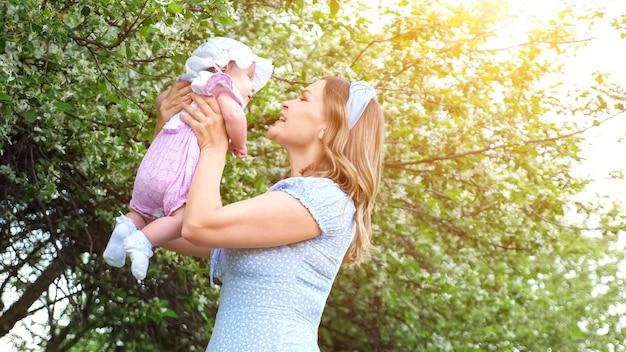 青いドレスを着た若い女性が腕を組んで面白い赤ん坊の娘が春の日に咲く庭に立っている陽気な笑顔で子供に話し、キスします