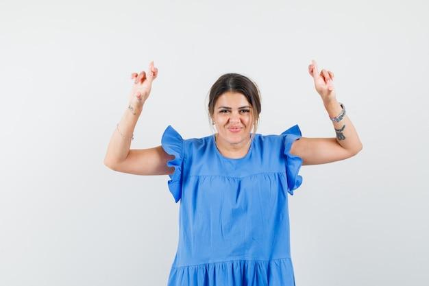 青いドレスを着た若い女性が指を交差させて陽気に見える