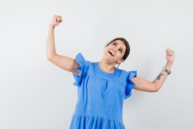 勝者のジェスチャーを示し、至福に見える青いドレスの若い女性