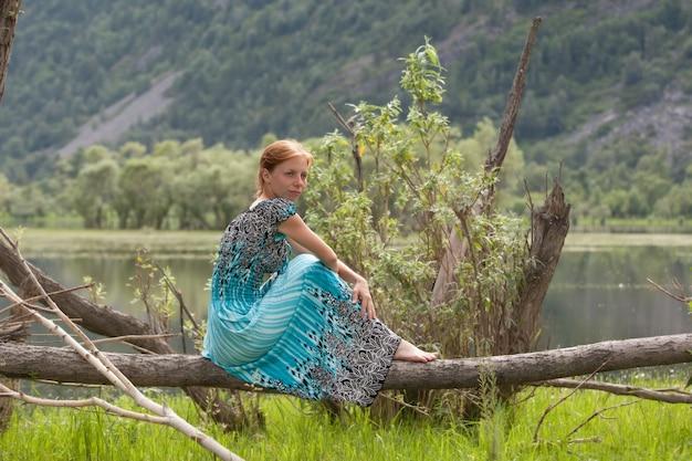 Молодая женщина в голубом платье, сидя на ветке дерева у воды.