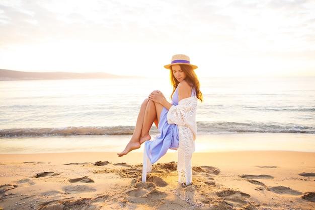 青いドレスを着た若い女性、椅子に座って、日の出