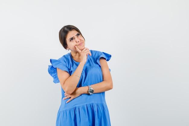 青いドレスを着た若い女性は、思考のポーズで立って、優柔不断に見えます