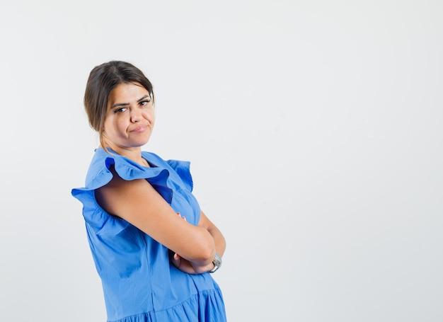 Молодая женщина в синем платье стоит со скрещенными руками и недовольна