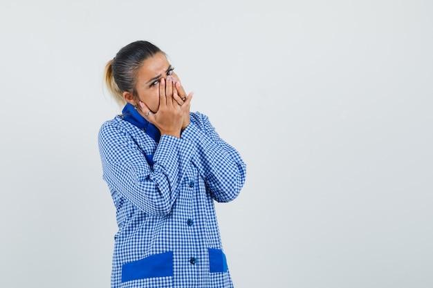 Молодая женщина в синей пижамной рубашке в клетку, закрывая рот руками и удивленно глядя, вид спереди.
