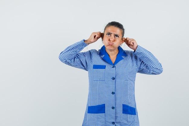 Молодая женщина в синей пижамной рубашке в мелкую клетку, тянет за уши пальцами и надувает щеки и выглядит мрачно, вид спереди.