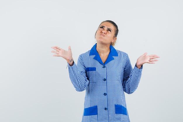 파란색 깅엄 파자마 셔츠에 젊은 여자가 뭔가를 들고 손을 들고, 뺨을 피고, 짜증이 나고, 전면보기를보고 있습니다.