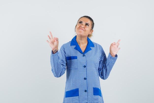 파란색 깅엄 파자마 셔츠에 젊은 여자가 두 손으로 확인 표시를 표시하고 예쁜, 전면보기를 찾고 있습니다.