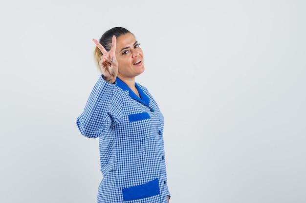 Молодая женщина в синей пижамной рубашке в клетку, показывая знак мира и выглядит красиво, вид спереди.