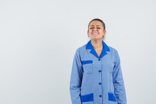 파란색 깅엄 파자마 셔츠에 젊은 여자가 똑바로 서서 포즈를 취하고 harried, 전면보기를보고 있습니다.