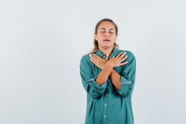 Молодая женщина в синей рубашке держит скрещенные руки на груди