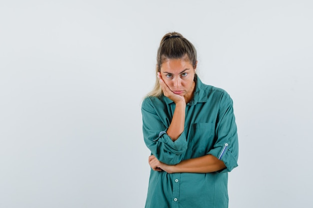 파란색 셔츠에 젊은 여자가 그녀의 팔꿈치에 기대어 지루해하는 동안 카메라를보고