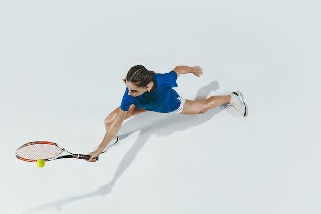 テニスをしている青いシャツを着た若い女性。白で隔離の屋内スタジオショット。上面図。