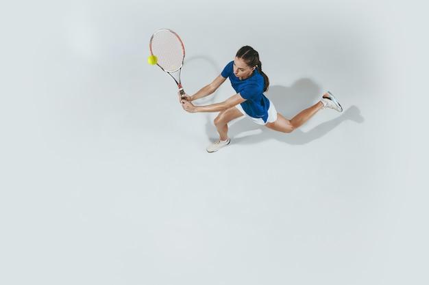 테니스 블루 셔츠에 젊은 여자. 그녀는 라켓으로 공을칩니다. 흰색 절연 실내 샷입니다. 젊음, 유연성, 힘 및 에너지. 부정적인 공간. 평면도.