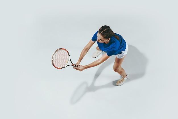 テニスをしている青いシャツの若い女性。彼女はラケットでボールを打つ。白で隔離された屋内ショット。若さ、柔軟性、パワー、そしてエネルギー。ネガティブスペース。上面図。