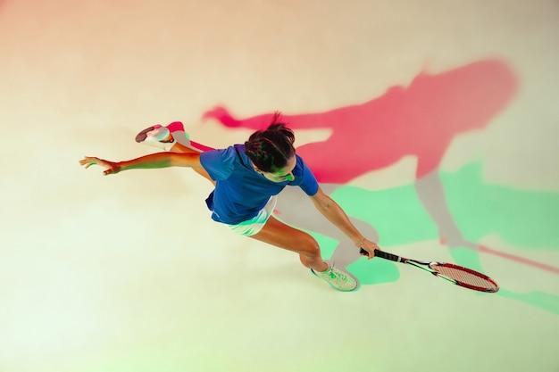 테니스 블루 셔츠에 젊은 여자. 그녀는 라켓으로 공을칩니다. 혼합 조명으로 실내 촬영. 젊음, 유연성, 힘 및 에너지. 평면도.