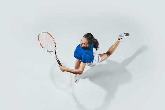テニスをしている青いシャツの若い女性。彼女はラケットでボールを打つ。上面図。