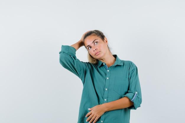 目をそらし、集中して見ながら頭に手を当ててポーズをとる青いシャツの若い女性