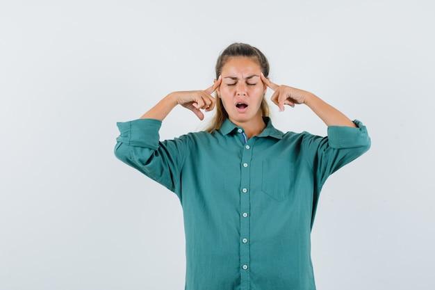 彼女の寺院をこすり、問題を抱えているように見える青いシャツの若い女性