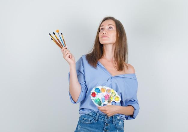 Молодая женщина в синей рубашке, шортах держит инструменты для рисования и выглядит обнадеживающей