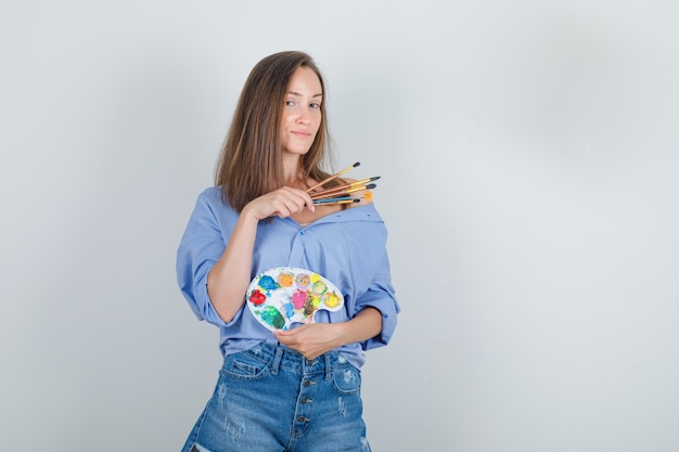 Молодая женщина в синей рубашке, шортах держит инструменты для рисования и выглядит гордо