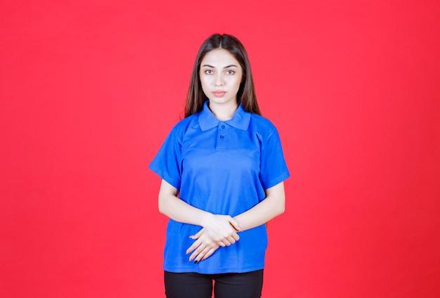 빨간 벽에 서 있는 파란 셔츠에 젊은 여자