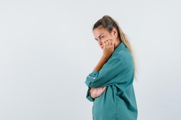 턱에 손 을와 서 불만족 찾고 파란색 셔츠에 젊은 여자.