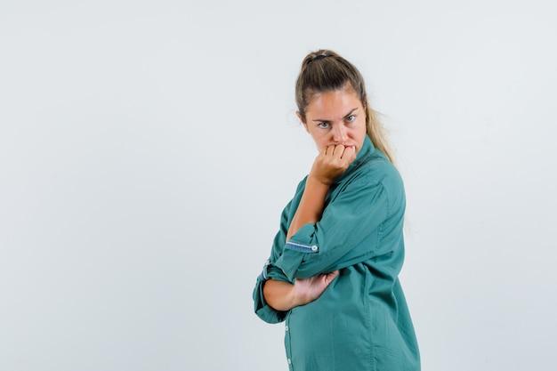 턱에 손으로 서 있고 분개 찾고 파란색 셔츠에 젊은 여자.