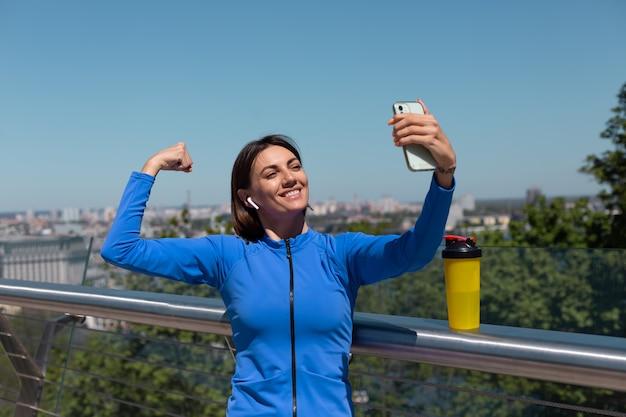青いスポーツの若い女性は、ワイヤレスヘッドフォンと携帯電話で暑い晴れた朝に橋の上で着て、社交のために自分撮り写真ビデオを撮って、彼女の筋肉の上腕二頭筋を示しています