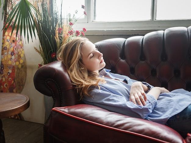 青い縞模様のシャツ、ジーンズの若い女性。思いやりのあるモデルの屋内の肖像画。自宅のソファに横たわっています。
