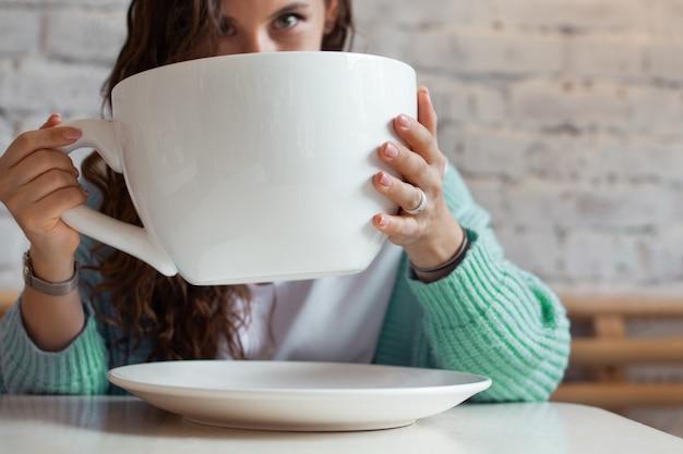 頭を抱えて眉をひそめ、家で巨大なお茶を持っている青いセーターの若い女性。女性は大きなカップの温かい飲み物を持って、頭痛を感じています。病気、病気、病気の概念。コピースペース