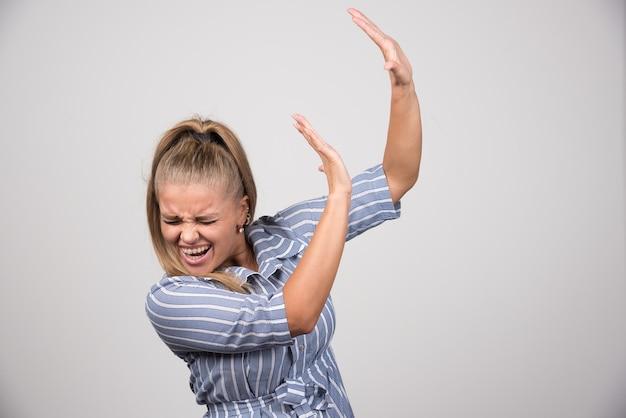 何かを拒否する青いセーターを着た若い女性。