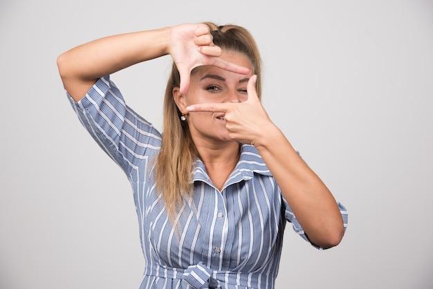 青いセーターを着た若い女性が手で写真を撮ります。