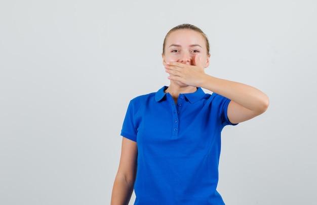 입에 손을 잡고 웃고 파란색 티셔츠에 젊은 여자
