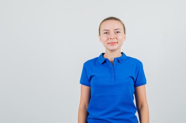 파란색 t- 셔츠보고 친절 하 게 찾고있는 젊은 여자