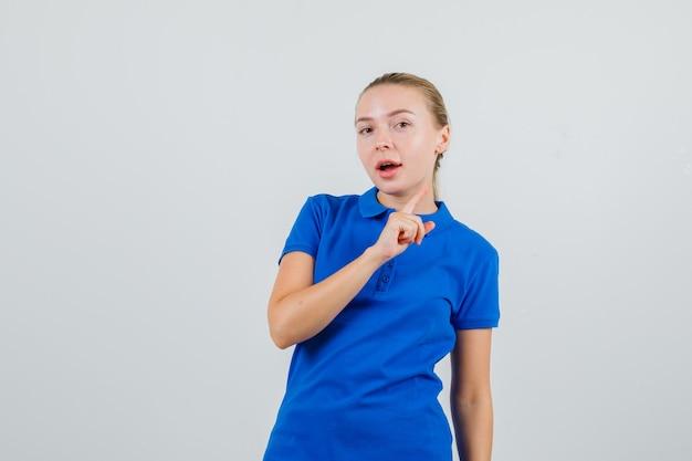 Молодая женщина в синей футболке смотрит вверх и с любопытством