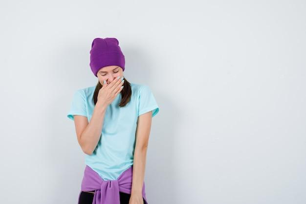 青いtシャツを着た若い女性、手で口を覆っている紫色の豆、笑って陽気に見える、正面図。