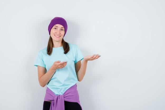 青いtシャツを着た若い女性、何かを表示し、陽気に見えるように手を伸ばす紫色のビーニー、正面図。