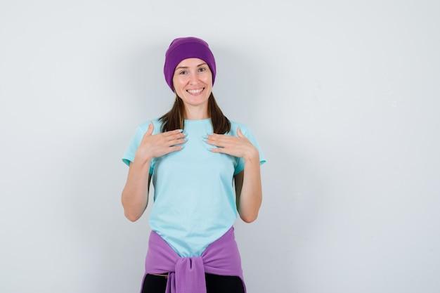 青いtシャツを着た若い女性、胸に手をかざし、陽気に見える紫色のビーニー、正面図。