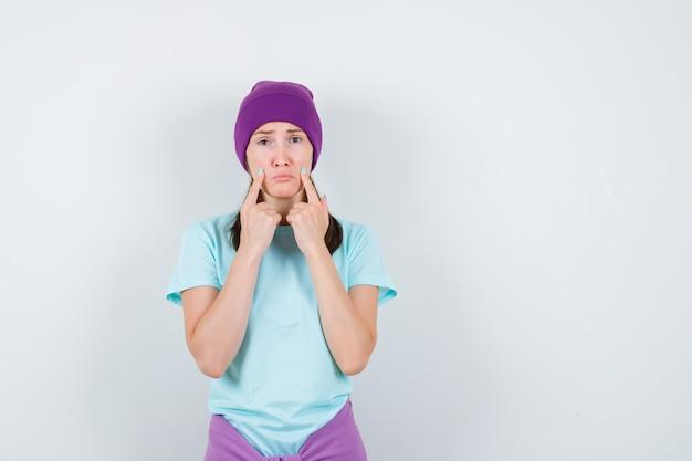 파란색 티셔츠를 입은 젊은 여성, 검지 손가락이 입 근처에 있는 보라색 비니, 입술을 구부리고 음침한 앞모습.