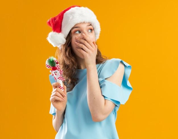 Молодая женщина в синем топе и шляпе санта-клауса, держащая рождественскую конфету, смотрит в сторону, потрясенная, прикрывая рот рукой
