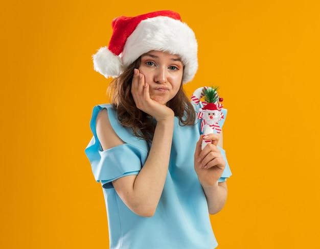 青いトップとサンタの帽子をかぶった若い女性は、彼女のあごに手で混乱し、不快に見えるクリスマスキャンディケインを保持しています