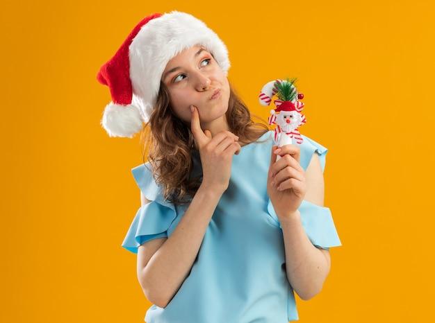 青いトップとサンタの帽子の若い女性が困惑して見上げるクリスマスのキャンディケインを保持しています