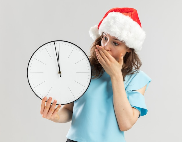 Молодая женщина в синем топе и шляпе санта-клауса держит настенные часы, глядя на него в шоке, прикрывая рот рукой