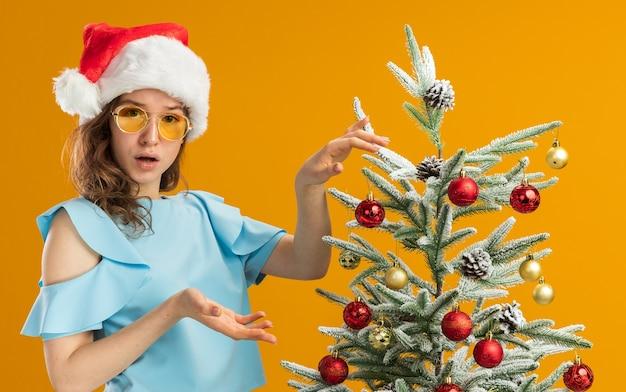 青いトップとオレンジ色の背景の上に立って混乱しているように見えるクリスマスツリーを飾る黄色いメガネを身に着けているサンタ帽子の若い女性
