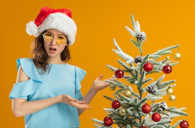 青いトップとサンタの帽子をかぶった若い女性がクリスマスツリーの横に立って、オレンジ色の壁に混乱しているように見える手の腕を提示します。