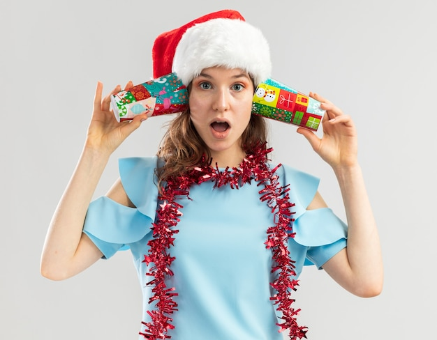 青いトップとサンタの帽子をかぶった若い女性が首に見掛け倒しでカラフルな紙コップを耳にかざして驚いた