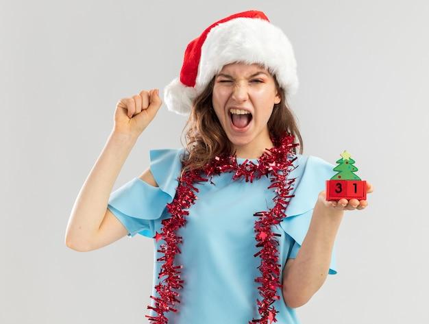 青いトップとサンタの帽子をかぶった若い女性が首に見掛け倒しでおもちゃの立方体を持って幸せな年の日付を握りこぶしを握り締めて狂った幸せを祝って叫ぶ