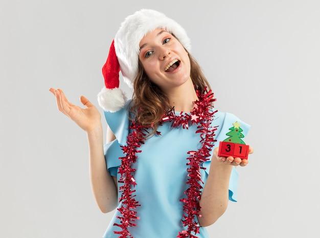 青いトップとサンタの帽子をかぶった若い女性が首に見掛け倒しのおもちゃの立方体を持って幸せで前向きな笑顔に見える幸せな年の日付