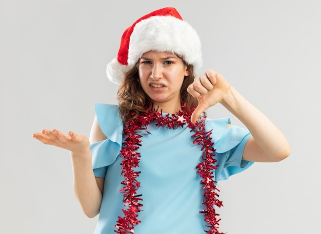 青いトップとサンタの帽子をかぶった若い女性が首に見掛け倒しをしていて、不機嫌になって混乱しているように見えます。
